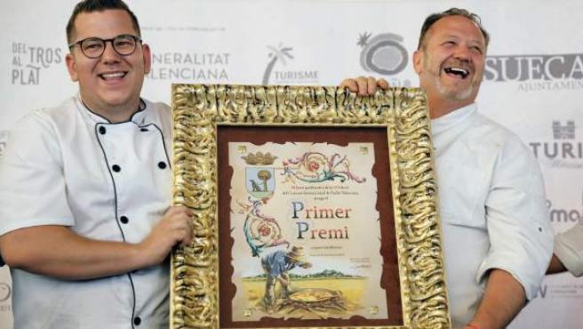 Los cocineros Raul Magraner (d) y su hijo Jordi, del restaurante Bon Aire de El Palmar, reciben el galardón tras ganar la 58 edición del Concurso Internacional de Paella de Sueca (Valencia).