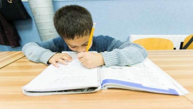 Un niño escribe en un libro de texto