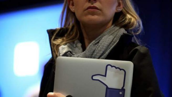 """Una mujer porta un ordenador portátil con un signo de """"me gusta"""" de Facebook."""