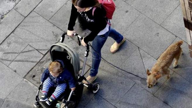 Mujer paseando el carrito con su bebé.
