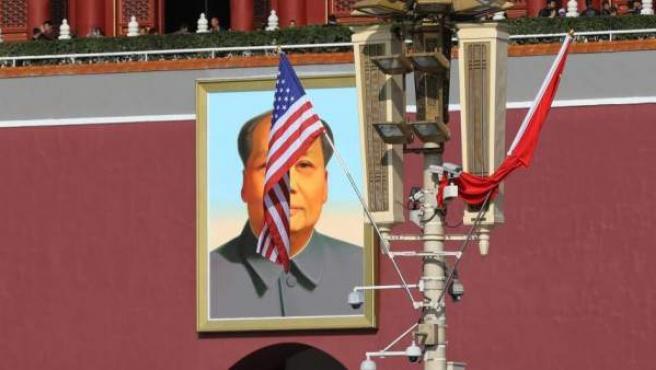 Una bandera de EE UU ondea en la plaza de Tiananmén de Pekín frente a un retrato de Mao Zedong.