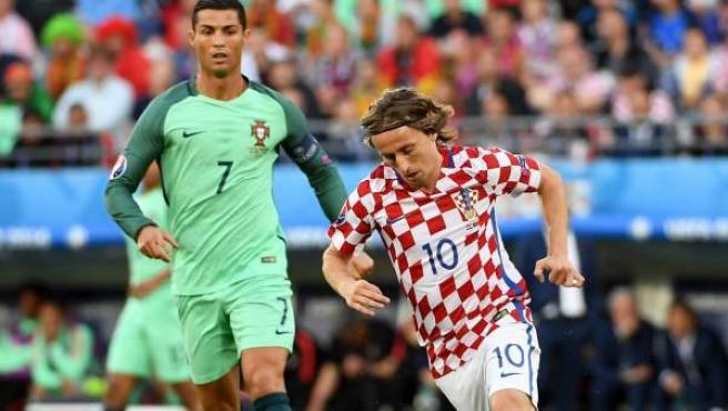 Modric controla un balón ante la mirada de Cristiano Ronaldo.