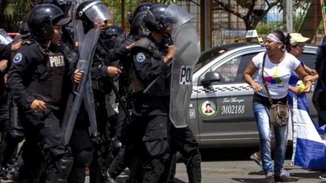 Miembros de la policía nacional bloquean una marcha opositora en Managua (Nicaragua).