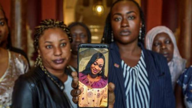 Un grupo de mujeres muestra en un móvil una foto de Maguette Mbeugou durante una concentración en repulsa por su asesinato en Bilbao.