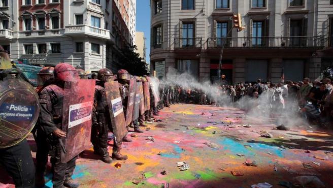 Grupos de independentistas han lanzado polvos de colores contra los Mossos d'Esquadra, desplegados para impedirles llegar hasta la Jefatura Superior de Policía de Barcelona.