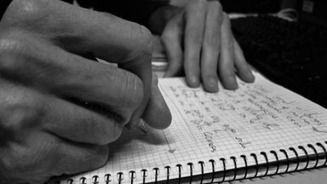 Una persona escribiendo en un cuaderno.