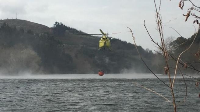 Imagen de un helicóptero intentando apagar un incendio con agua del pantano.