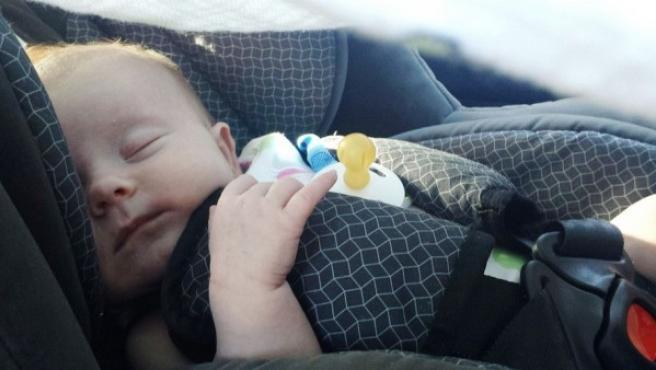 <p>Un bebé duerme en la silla infantil de un coche.</p>
