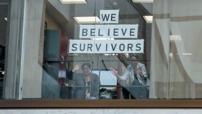 """Empleados del Congreso de EE UU, en Washington, observan a manifestantes contra la confirmación del nominado a la Corte Suprema Brett Kavanaugh, tras un mensaje en el que se lee """"Creemos a las supervivientes""""."""