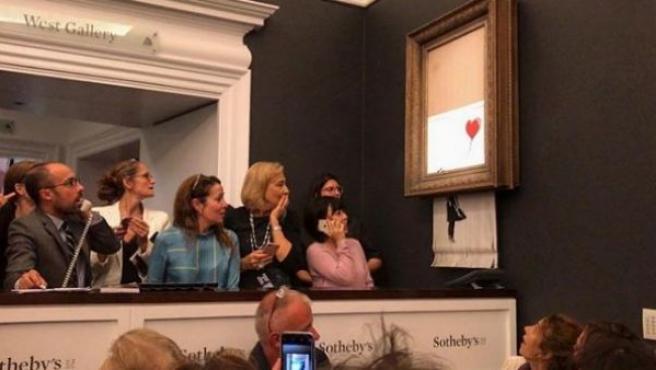 Momento en el que el lienzo de Banksy 'Niña con globo' pasaba por una trituradora de papel.
