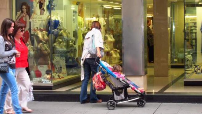 Una mujer mira un escaparate con su hija en una silla de paseo.