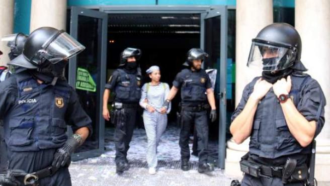 Agentes de los Mossos d'Esquadra desalojan a una activista de la PAH de la sede de Bankia en la calle Casp de Barcelona.