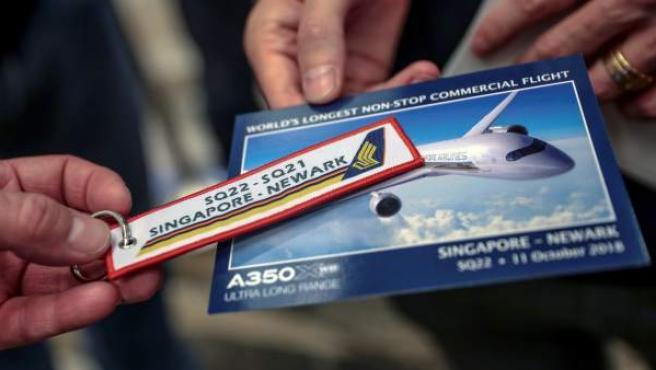 Imagen de un llavero y una postal conmemorativos del vuelo SQ22 de la aerolínea Singapore Airlines.