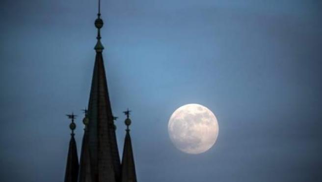 La luna llena, junto a la cúpula de una iglesia la capital de la República Checa, Praga.