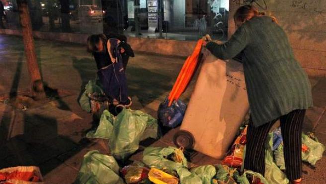 Dos mujeres buscan comida en un contenedor de basuras en Madrid