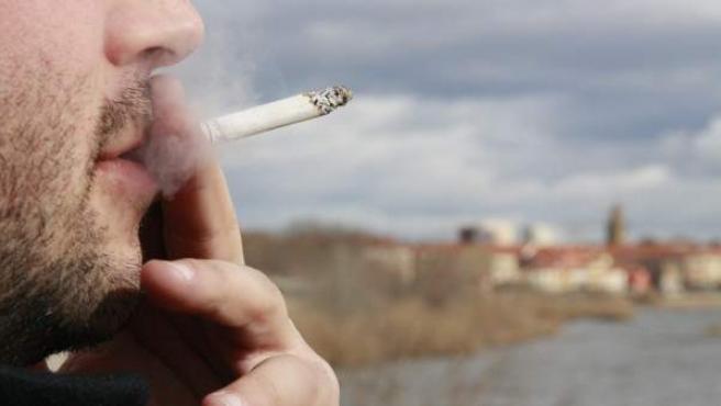 Un hombre, fumando un cigarrillo.