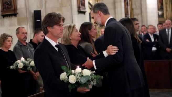 El rey Felipe VI (d) saluda a familiares de víctimas a su llegada a la Parroquia de Nuestra Señora de los Dolores de Manacor.