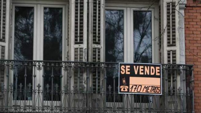 """El cartel de """"Se vende"""" en el balcón de una vivienda."""