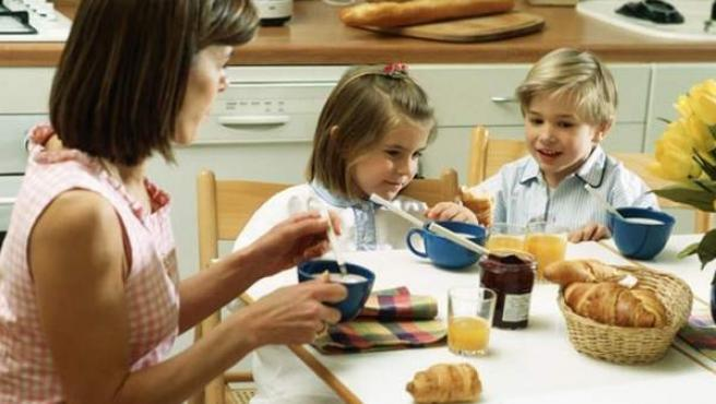 Una madre, desayunando junto a sus dos hijos.