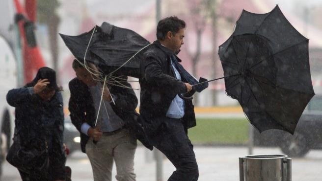 Varias personas sujetan sus paraguas intentando que no se les vuele debido al fuerte viento y a la lluvia en Málaga.