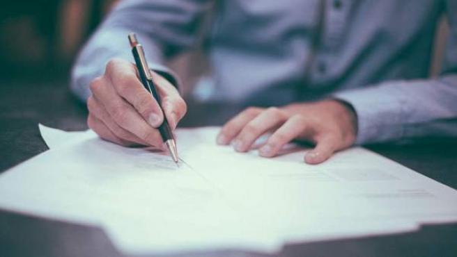 Una persona firmando el documento de una hipoteca.