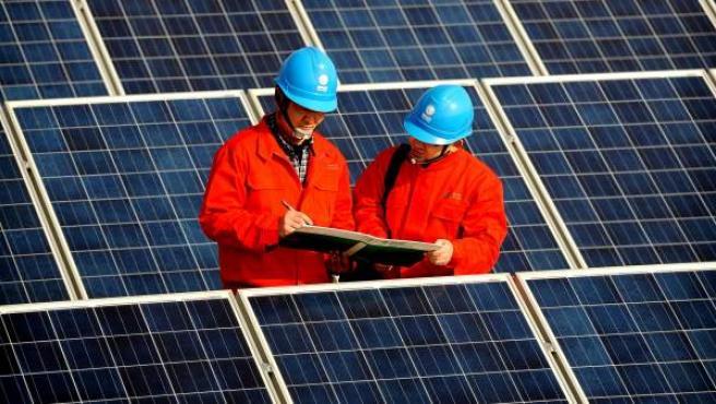 Imagen de dos operarios en una instalación de placas solares.