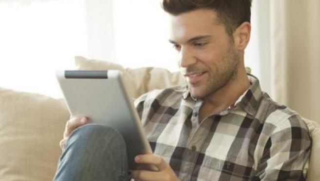 Un hombre relajado en su sofá con su tablet.