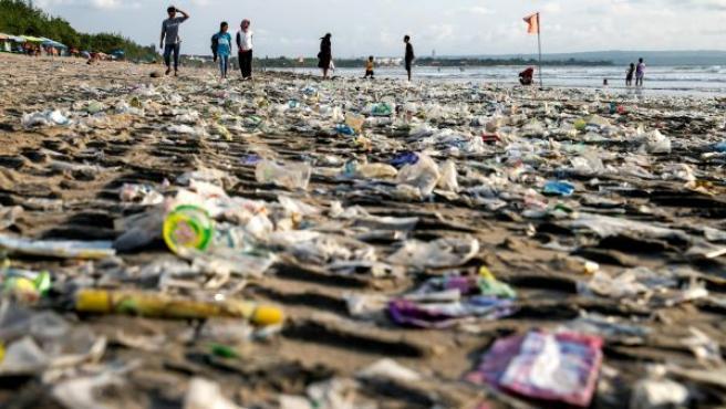 Varias personas caminan por la playa sobre una alfombra de restos de plástico usado que llegaron a la costa traídos por fuertes olas en la playa de Kuta, en Bali (Indonesia).