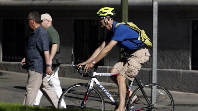Un hombre se transporta en bicicleta por la ciudad.