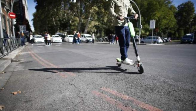 Un hombre circula en patinete eléctrico por Madrid.