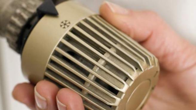Una mujer regulando la temperatura de un radiador.
