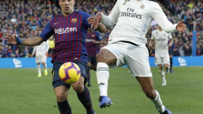 Raphael Varane y Luis Suárez pugnan por un balón durante el Barcelona-Real Madrid.