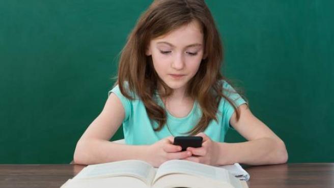 Una niña usa su teléfono móvil.