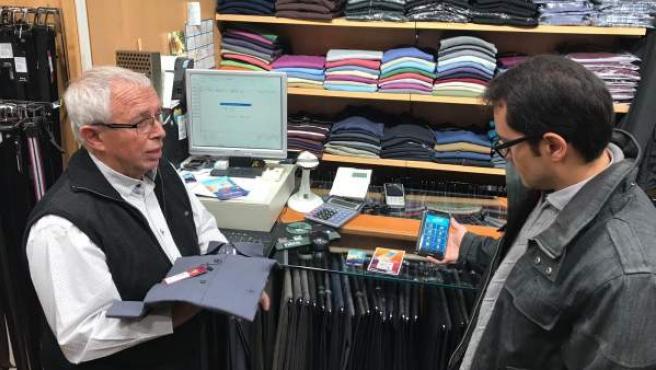 Un cliente usa Viba.Barcelona en una compra en el barrio de Sant Antoni.