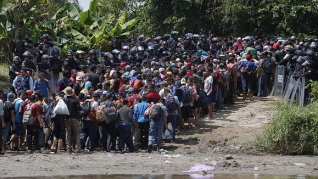 Policías antimotines mexicanos dejan pasar a cientos de migrantes hondureños que cruzaron a pie el río Suchíate.