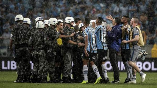 Los jugadores de Gremio protestan al árbitro, que tuvo que ser escoltado