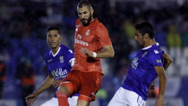Karim Benzema entre dos jugadores del Melilla durante el partido de ida de los dieciseisavos de final de la Copa del Rey.