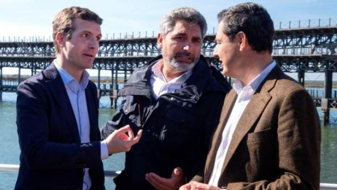 Pablo Casado (i), acompañado del presidente del PP-A, Juanma Moreno (d) y de Juan José Cortés, durante el acto en Huelva.