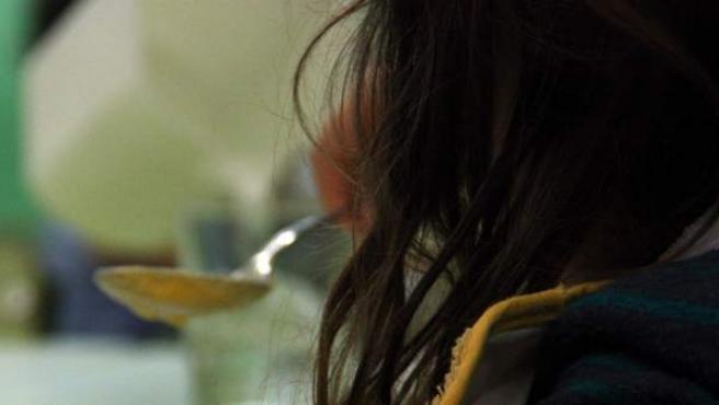 Una niña en un comedor escolar.