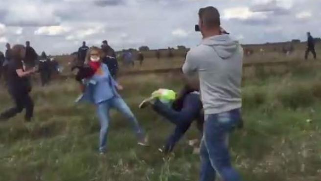 Imagen de la periodista húngara poniendo la zancadilla a un refugiado en Hungría.