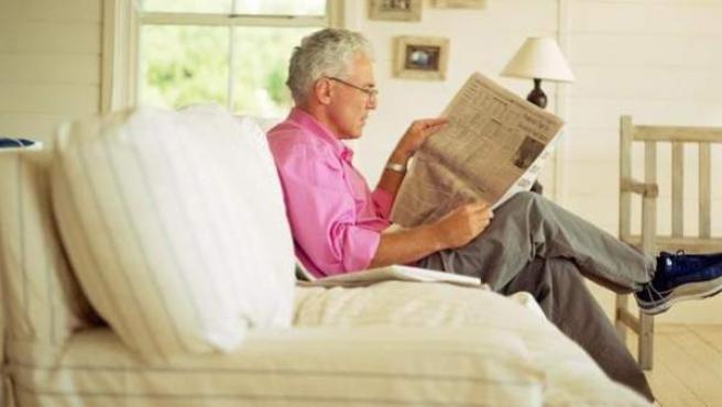 Una persona mayor lee en el salón de su casa.