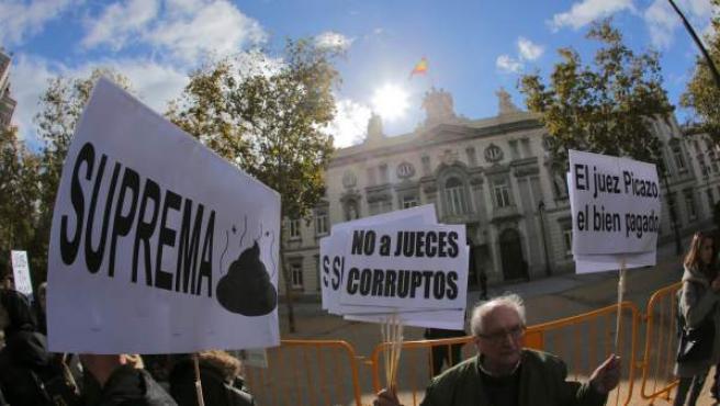 Un grupo de manifestantes protesta contra la decisión del Tribunal Supremo sobre las hipotecas, esta mañana frente al mismo edificio.