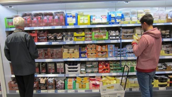 Consumidores leen el etiquetado de productos en un supermercado.