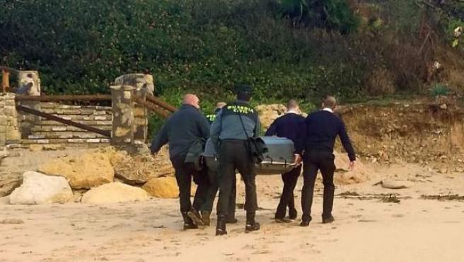 Agentes retirando uno de los cadáveres encontrados tras el naufragio de una patera en Cádiz.
