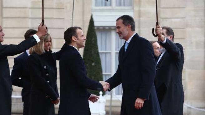 El presidente francés, Emmanuel Macron, saluda al rey Felipe VI a su llegada al Elíseo para participar en los actos del centenario del fin de la I Guerra Mundial.