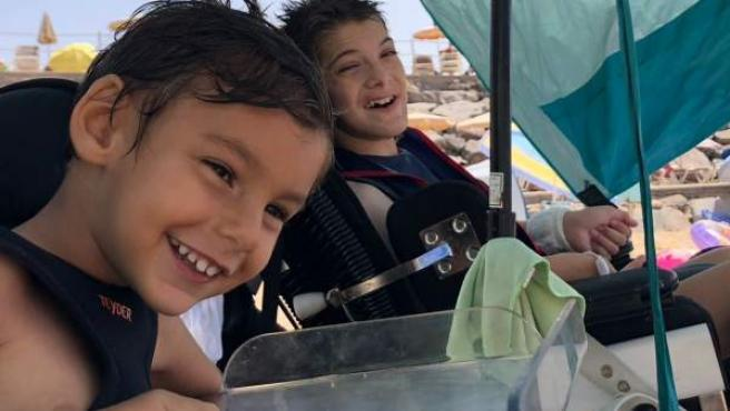 El pequeño Ibai, junto a su hermano mayor, César, en una salida familiar a la playa. Ambos menores padecen el síndrome neurológico Lesch Nyhan. (Sus padres han autorizado expresamente la publicación de la imagen de sus hijos sin distorsionar).