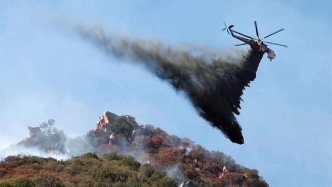 """Un helicóptero descarga agua sobre el incendio forestal """"Woolsey"""", en Malibú, California (EE UU)."""