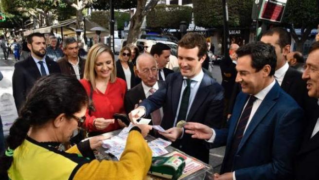 El presidente del Partido Popular, Pablo Casado (c), compra un décimo de la ONCE mientras pasea por el centro de Almería.