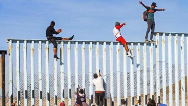 Members of the Central American caravan scale the border wall with the United States in Tijuana, Mexico.