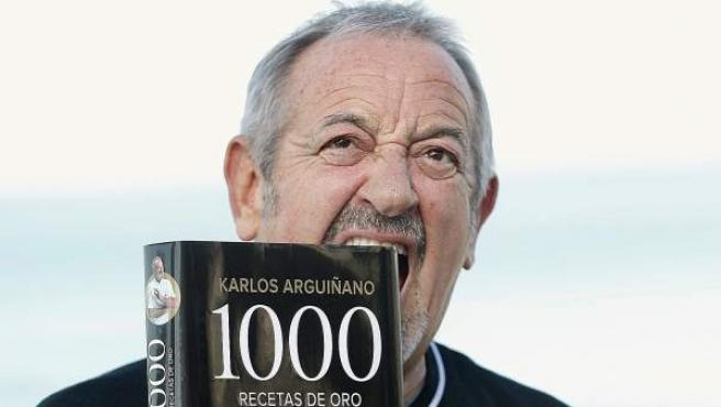 El cocinero Karlos Arguiñano posa con su nuevo libro de recetas en su restaurante de Zarautz.